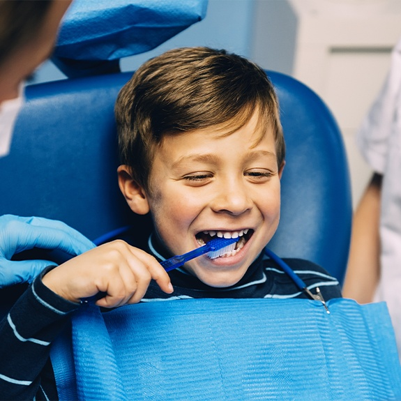 Child in dental chair brushing teeth
