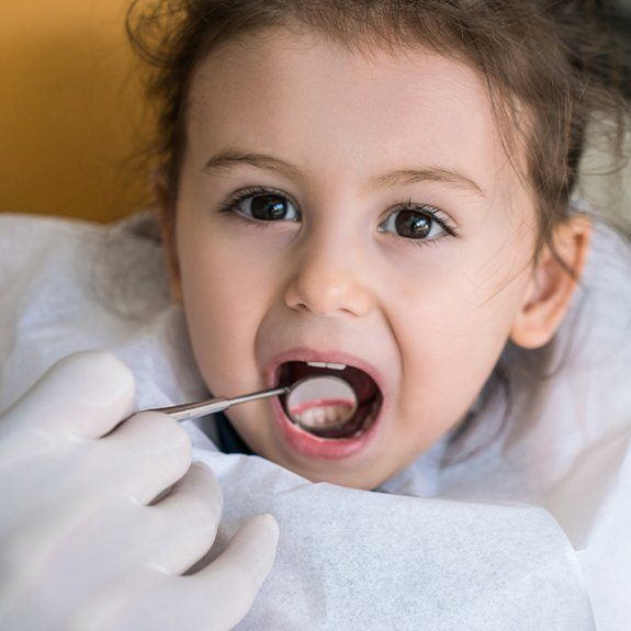 Young girl receiving dental exam after tooth-colored filling placement