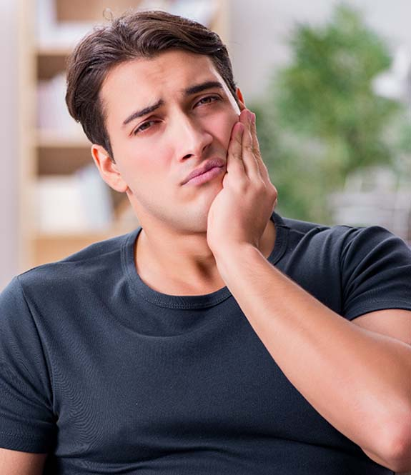 Man in need of emergency dentistry holding jaw