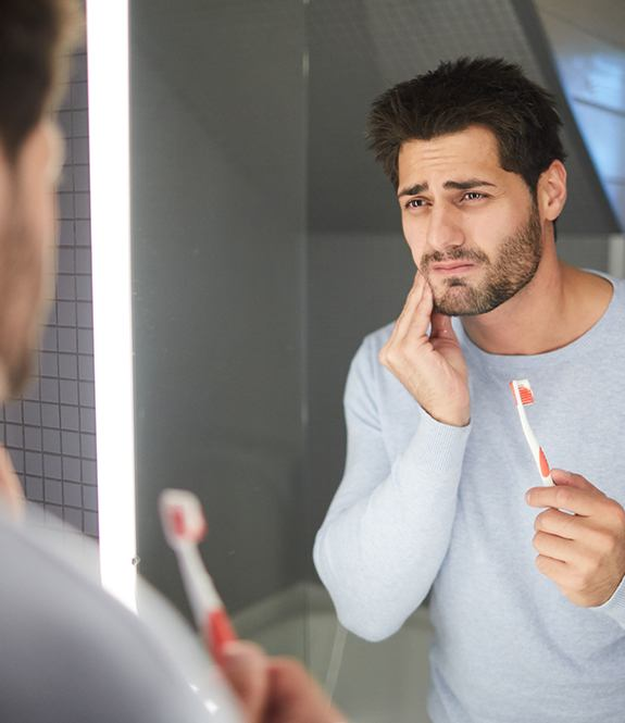Man holding cheek after painful brushing needs periodontal therapy