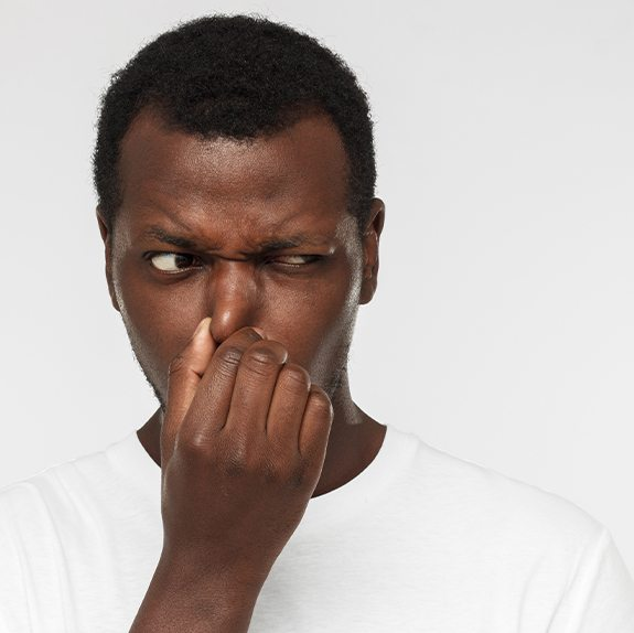 Man plugging nose due to bad breath