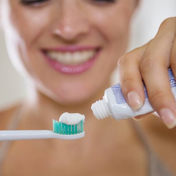 Woman placing toothpaste on toothbrush