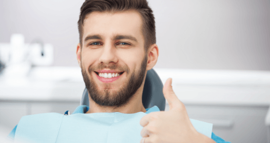 Smiling man giving thumbs up after dental checkup