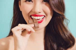 young woman biting into a piece of chocolate
